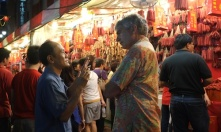 People speak in front of a waxed sausage store at Chinatown, Singapore