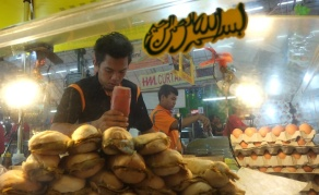 Food for thought! A man squeezes ketchup on a local sandwich called roti john