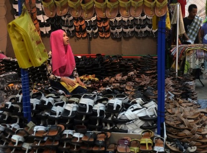 A girl selling shoes looks at a customer